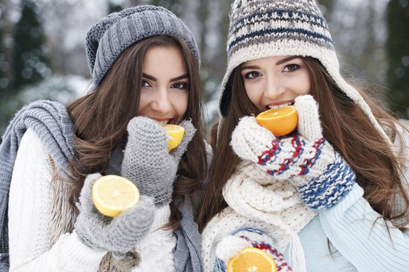 Das Bild zeigt zwei Mädels die firsches Obst/Vitamine zu sich nehmen