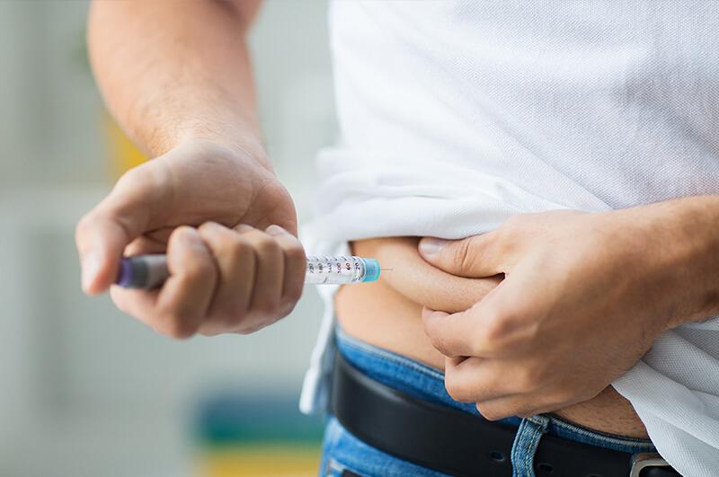 zu sehen ist eine Person welche sich eine Insulinspritze gibt