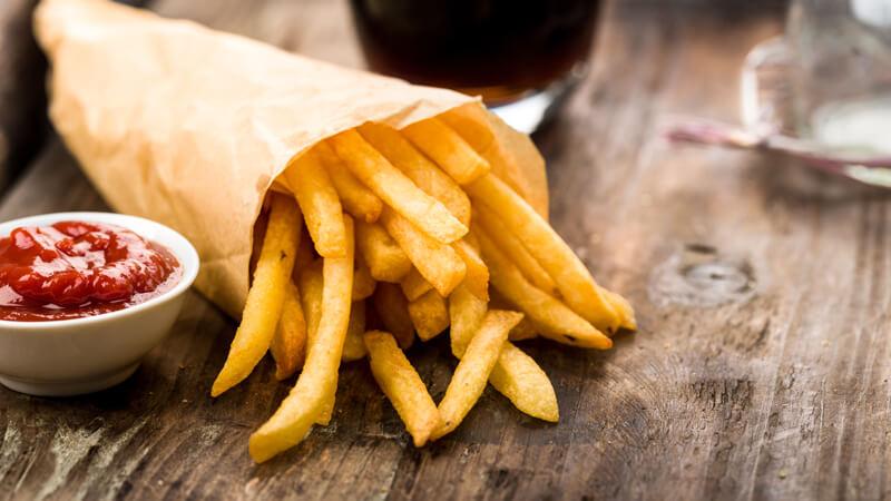 Das Bild zeigt eine Pommestüte und Ketchup